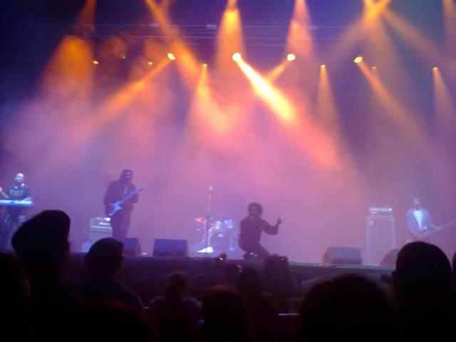 The Coup al principio, en quinteto, entre tinieblas, con su líder Boots Riley acuclillado (imagen de móvil: O.C.E.).